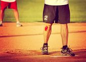 a man's legs on a baseball or softball field with a big scrape toned with a retro vintage instagram