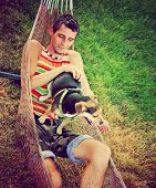 a young man in a hammock cuddling with his chihuahua beagle mix dog toned with a retro vintage insta