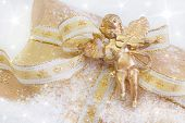 Close Up Of Golden Present Box With Angel Playing Violin For Christmas On Snowy Background