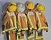 foto of firemen  - Firefighters uniforms hanging on coat hooks on wall - JPG