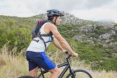 Side view of an athletic young man mountain biking