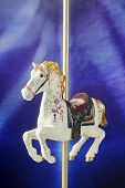 A white, antiqued carousel horse against a lighted blue/purple background.