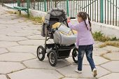 little girl with baby carriages