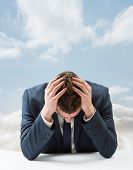 Businessman with head in hands against cloudy sky