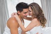 Side view of romantic young couple sitting in bed at home