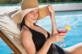 Portrait of beautiful young woman holding drink by swimming pool