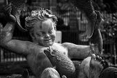 picture of ero  - a black and white closeup photo of an angel in a fountain - JPG