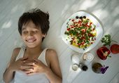 Kid enjoying summer organic kitchen preparing food with vegetable ingredients and creamy cheese