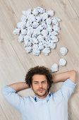Crumpled Papers Over Man's Head Lying On Floor