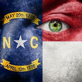 Flag Painted On Face With Green Eye To Show North Carolina Support