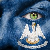 stock photo of bayou  - Flag painted on face with green eye to show Louisiana support - JPG