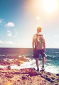 stock photo of sun flare  - Young man wearing a backpack standing on rocks overlooking the ocean looking down at the white surf in contemplation backlit by the flare of a hot tropical sun - JPG