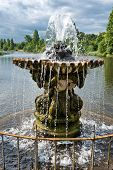 Ornamental stone fountain covered in moss with a jet of cascading water at the head of a lake or pon