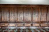 Old medieval wood paneling covering a wall in a historical country house with a diamond pattern marb