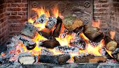 Glowing coals in a wood fire with fiery orange flames in a brick hearth or fireplace with a wrought iron backplate, close up backgroud view