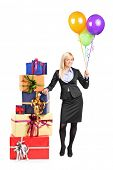 Full length portrait of a businesswoman standing by a pile of presents and holding balloons isolated