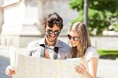 Happy couple of tourists holding a map
