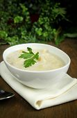 Leek and potato soup in a white bowl with parsley on top