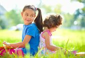 Two little girls are reading books while sitting on green grass, outdoor shoot