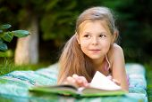 Cute little girl is reading a book while laying on green grass
