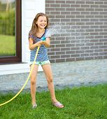Happy girl pouring water from a hose on backyard