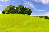 stock photo of bonnes  - Conceptual image of a pathway leading round a hill to the summit with vibrant green grass blue skies with white clouds and room for copy space - JPG