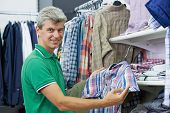 man choosing shirt during shopping at garments clothing shop