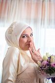 picture of shy girl  - Shy muslim girl smiling with flowers in her hands - JPG