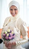 Happy bride in islamic clothes posing with flowers indoors
