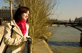 Beautiful Woman In Paris On The Seine Embankment Near The Pedestrian Bridge Pont Des Arts