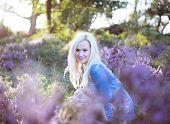 Beautiful blonde woman on the lavender field wearing jeans jacket .