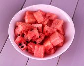 Slices of watermelon in pink plate on wooden background