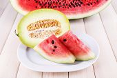 Slices of watermelon on plate on wooden background
