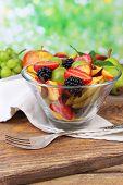 fresh tasty fruit salad on wooden table, on nature background