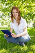 Pretty redhead using her tablet pc in the park on a sunny day