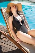View of beautiful young woman in bikini relaxing by swimming pool