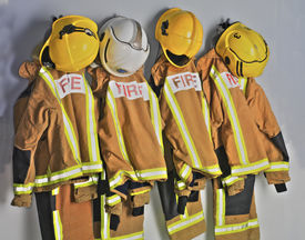 stock photo of firefighter  - Firefighters uniforms hanging on coat hooks on wall - JPG