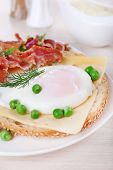 Sandwich with poached egg, cheese and bacon on plate on wooden background