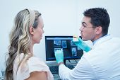 foto of prosthesis  - Side view of male dentist showing woman prosthesis teeth - JPG