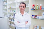 foto of coat  - Portrait of a smiling student in lab coat with arms crossed in the pharmacy - JPG