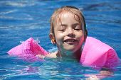 Joyful little girl swimming in the pool