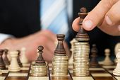picture of coins  - Midsection of businessman placing chess pieces on stacked coins - JPG