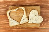 Slice of cereal toast bread with cut out heart shape on wooden cutting board