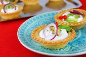 Tartlets with greens and vegetables with sauce on plate and tray