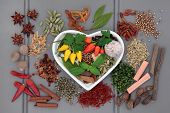 Spice and herb selection in a heart shaped dish and loose over wooden grey  background.