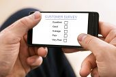 Person Filling Customer Survey Form On Mobile Phone