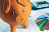 closeup of a piggy bank on a desk with bills and charts and a calculator in the background