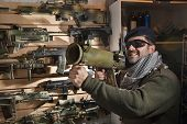 picture of beret  - Arms merchant in the beret and sunglasses with the jet grenade launcher on the weapon display background - JPG