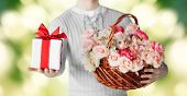 holidays, people, feelings and greetings concept - close up of man holding basket full of flowers and gift box over green background