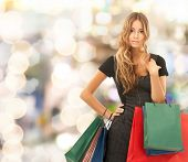people, holidays and sale concept - young happy woman with shopping bags over lights background